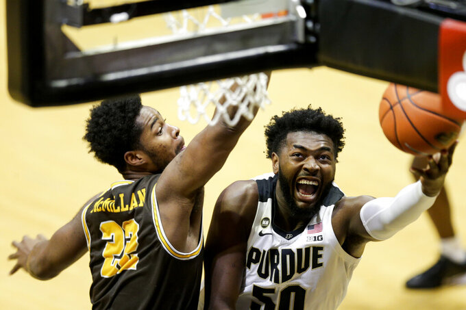 Purdue forward Trevion Williams (50) goes up for a layup past Valparaiso forward Mileek McMillan (22) during the first half of an NCAA college basketball game Friday, Dec. 4, 2020, in West Lafayette, Ind. (Nikos Frazier/Journal & Courier via AP)