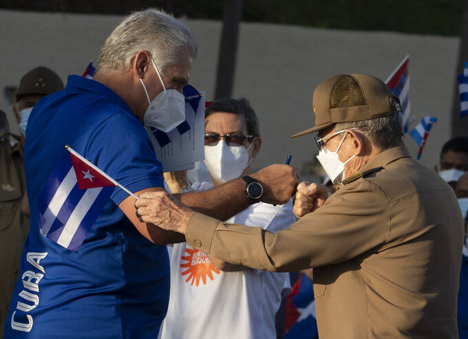 Raul Castro, right, greets Cuba's President Miguel Diaz Canel, during a cultural-political event on the seaside Malecon Avenue with thousands of people in a show of support for the Cuban revolution six days after the uprising of anti-government protesters across the island, in Havana, Cuba, Saturday, July 17, 2021. (AP Photo/Eliana Aponte)