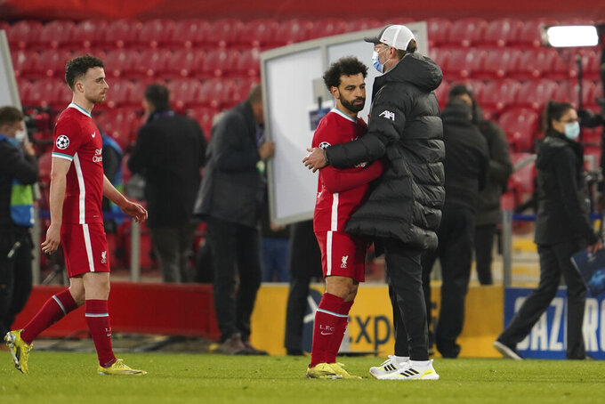 Liverpool's manager Jurgen Klopp, right, greets Liverpool's Mohamed Salah at the end of the Champions League quarter final second leg soccer match between Liverpool and Real Madrid at Anfield stadium in Liverpool, England, Wednesday, April 14, 2021. (AP Photo/Jon Super)