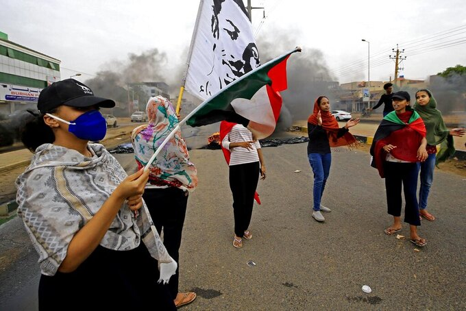 Sudanese women carry national flags during a demonstration to commemorate the first anniversary of a deadly crackdown carried out by security forces on protesters during a sit-in outside the army headquarters, in Khartoum, Sudan, Saturday, May 23, 2020. (AP Photo/ Marwan Ali)