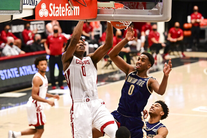 Washington State center Efe Abogidi (0) dunks the ball as Montana State forward Abdul Mohamed (0) defends in the first half of an NCAA college basketball game, Friday, Dec. 18, 2020, in Pullman, Wash. (Pete Caster/Lewiston Tribune via AP)