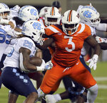 North Carolina's D.J. Jones (26) is stopped at the line of scrimmage by Virginia Tech's Norell Pollard (3) during the second half of an NCAA college football game Friday, Sept. 3, 2021, in Blacksburg, Va. (Matt Gentry/The Roanoke Times via AP)