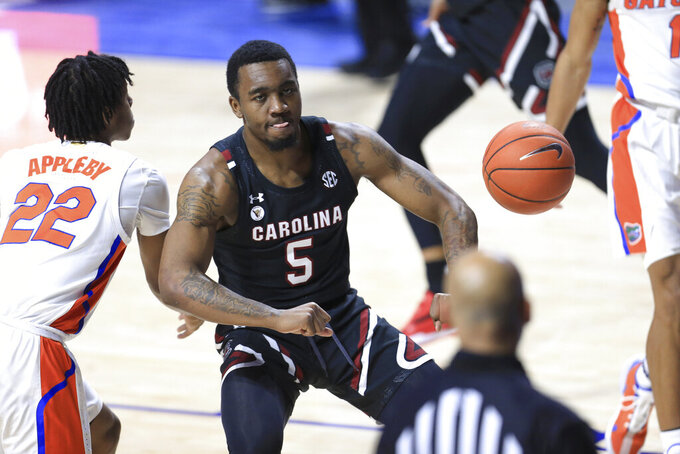 South Carolina guard Jermaine Couisnard (5) celebrates after a dunk next to Florida guard Tyree Appleby (22) during the second half of an NCAA college basketball game Wednesday, Feb. 3, 2021, in Gainesville, Fla. (AP Photo/Matt Stamey)