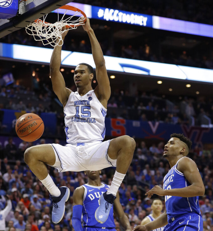 North Carolina's Garrison Brooks (15) dunks against Duke's Javin DeLaurier (12) during the first half of an NCAA college basketball game in the Atlantic Coast Conference tournament in Charlotte, N.C., Friday, March 15, 2019. (AP Photo/Nell Redmond)