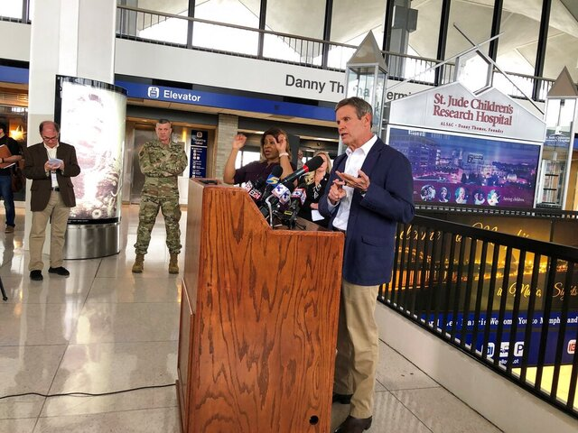 Tennessee Gov. Bill Lee (right, at podium) speaks to reporters at Memphis International Airport about the state's response to the new coronavirus on Friday, March 27, 2020, in Memphis, Tenn. (AP Photo/Adrian Sainz).