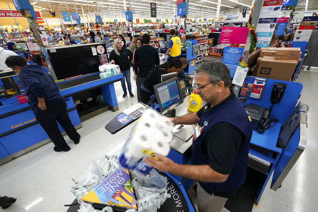 FILE - In this Nov. 9, 2018, file photo Walmart associate Javaid Vohar, right, checks out customers at a Walmart Supercenter in Houston. Walmart says it is testing higher wages for new hourly positions at 500 of its U.S. stores as part of an overall strategy to better empower its staff. (AP Photo/David J. Phillip, File)