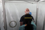 Jim Zoller, top, gets a rapid COVID-19 test from June Lopez, Dignity GoHealth medical assistant, before a United Airlines flight to Hawaii at San Francisco International Airport in San Francisco, Thursday, Oct. 15, 2020. Coronavirus weary residents and struggling business owners in Hawaii will be watching closely as tourists begin to return to the islands on Thursday without having to self-quarantine upon arrival. (AP Photo/Jeff Chiu)