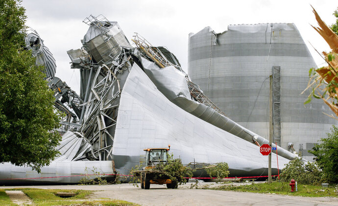 Iowa Department of Transportation workers help with tree debris removal as grain bins from the Archer Daniels Midland facility are seen severely damaged in Keystone, Iowa, on Wednesday, Aug. 12, 2020. A storm slammed the Midwest with straight line winds of up to 100 miles per hour on Monday, gaining strength as it plowed through Iowa farm fields, flattening corn and bursting grain bins still filled with tens of millions of bushels of last year's harvest. (Jim Slosiarek/The Gazette via AP)
