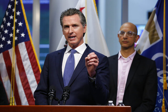 FILE - In this March 17, 2020 file photo California Health and Human Services Agency Director Dr. Mark Ghal, right, looks on as California Gov. Gavin Newsom talks at a news conference at the Governor's Office of Emergency Services in Rancho Cordova Calif. On Tuesday, Dec. 15, 2020 Newsom said California is distributing 5,000 body bags mostly to the hard-hit Los Angeles and San Diego areas and has 60 refrigerated 53-foot trailers standing by as makeshift morgues in anticipation of a surge of coronavirus deaths from hospitalizations that now are double the summertime peak and threaten to soon overwhelm the hospital system. (AP Photo/Rich Pedroncelli, Pool, File)