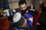 Israeli medical teams administer the Pfizer-BioNTech COVID-19 vaccine to Palestinians at the Qalandia checkpoint between the West Bank city of Ramallah and Jerusalem on Tuesday, Feb. 23, 2021. While moving aggressively to vaccinate its adult population, including Arab citizens, Israel has not shared significant quantities of vaccines with the Palestinians in the West Bank. Tuesday's vaccinations were offered to Palestinians who have Israeli residency rights but live in the West Bank. (AP Photo/Oded Balilty)