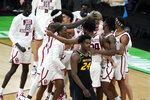 Oklahoma players celebrate as Missouri forward Kobe Brown (24) walks off the court after a first-round game in the NCAA men's college basketball tournament at Lucas Oil Stadium, Saturday, March 20, 2021, in Indianapolis. Oklahoma won 72-68. (AP Photo/Darron Cummings)