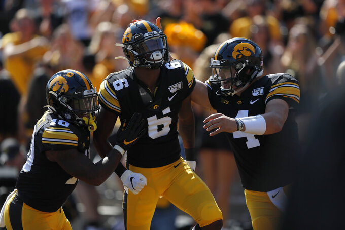 Iowa running back Mekhi Sargent, left, and quarterback Nate Stanley, right, congratulate wide receiver Ihmir Smith-Marsette, center, after his touchdown during the first half of an NCAA college football game against Rutgers, Saturday, Sept. 7, 2019, in Iowa City. (AP Photo/Matthew Putney)
