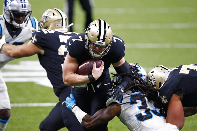 New Orleans Saints quarterback Taysom Hill (7) carries against Carolina Panthers free safety Tre Boston (33) in the first half of an NFL football game in New Orleans, Sunday, Oct. 25, 2020. (AP Photo/Butch Dill)