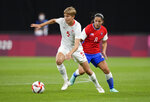 Canada's Quinn, left, and Chile's Karen Araya battle for the ball during a women's soccer match at the 2020 Summer Olympics, Saturday, July 24, 2021, in Sapporo, Japan. (AP Photo/Silvia Izquierdo)