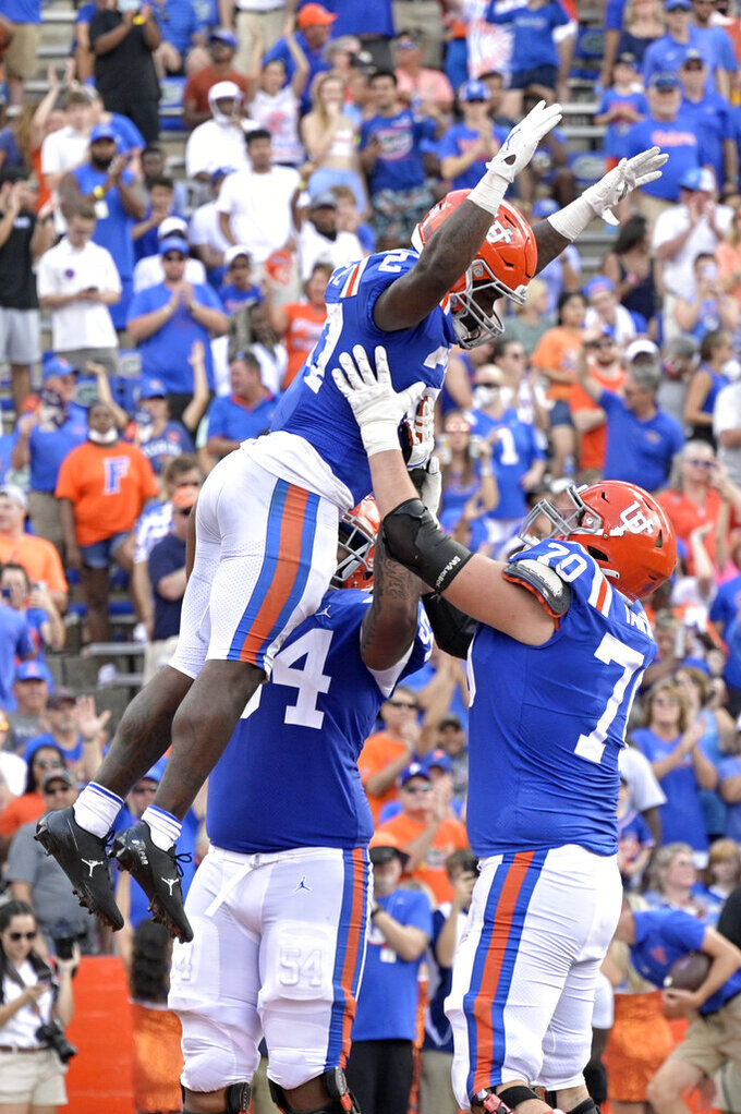 Florida running back Dameon Pierce (27) is lifted in the air by offensive linemen Gerald Mincey (54) and Michael Tarquin (70) after Pierce rushed for a 1-yard touchdown during the second half of an NCAA college football game against Vanderbilt, Saturday, Oct. 9, 2021, in Gainesville, Fla. (AP Photo/Phelan M. Ebenhack)