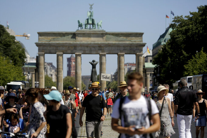 A demonstrator carries a sign reading 'Freedom' in front of the Brandenburg gate as he attends a demonstration with the slogan 'The end of the pandemic - freedom day' - against coronavirus restrictions in Berlin, Germany, Saturday, Aug. 1, 2020. It comes amid increasing concern about an upturn in infections in Germany. (AP Photo/Markus Schreiber)