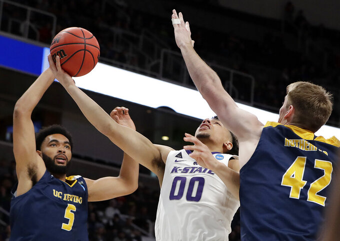 Kansas State guard Mike McGuirl, center, shoots between UC Irvine forward Jonathan Galloway (5) and forward Tommy Rutherford (42) during the first half of a first round men's college basketball game in the NCAA Tournament Friday, March 22, 2019, in San Jose, Calif. (AP Photo/Chris Carlson)