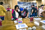 FILE - In this May 19, 2018 photo tourists Randy Wilkie and Keya Cole from Buffalo, New York, check out the offerings of cannabis at one of the MedMen cannabis dispensaries in Los Angeles. Marijuana stocks have come down hard from their highs a year ago, and the skid isn't just spooking investors. On Tuesday, Oct. 8, 2019, MedMen Enterprises Inc., which sells legal cannabis in California and 11 other states, backed out of a blockbuster deal to buy PharmaCann, a Chicago-based marijuana company with operations in eight states. (AP Photo/Richard Vogel,File)