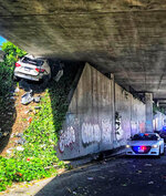 In this photo provided by the California Highway Patrol is the scene where a man fleeing from the CHP totaled his girlfriend's Maserati SUV after he careened up an embankment and slammed into the underside of an overpass, wedging the car under a freeway in Oakland, Calif., on Monday, April 12, 2021. (California Highway Patrol via AP)