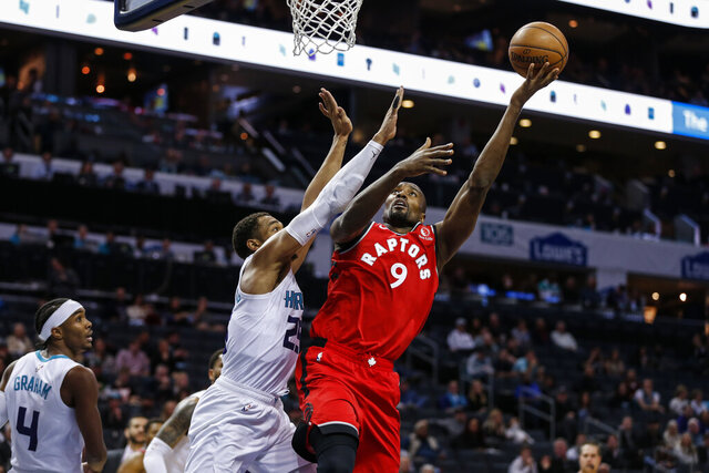 Toronto Raptors forward Serge Ibaka, right, shoots over Charlotte Hornets forward P.J. Washington during the second half of an NBA basketball game in Charlotte, N.C., Wednesday, Jan. 8, 2020. Toronto won 112-110 in overtime. (AP Photo/Nell Redmond)