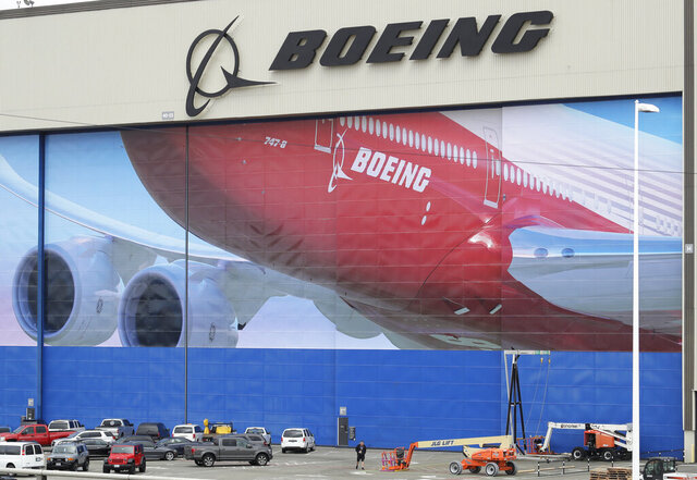 FILE - In this Monday, March 23, 2020, file photo, a worker walks near a mural of a Boeing 747-8 airplane at the company's manufacturing facility in Everett, Wash., north of Seattle. In an email to Washington employees on Sunday, April 5, 2020, the company says due to coronavirus concerns, it is extending a planned two-week shutdown rather than reopening Wednesday, April 8. The decision affects about 30,000 of Boeing's 70,000 employees in the state. Employees are receiving their regular salaries during the two-week shutdown, but will have to transition to vacation or sick leave after that. (AP Photo/Ted S. Warren, File)