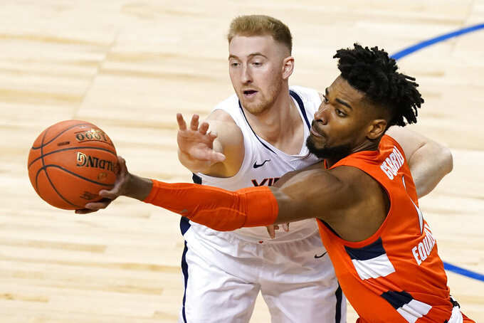 Syracuse forward Quincy Guerrier, right, passes the ball past Virginia forward Sam Hauser (10) during the first half of an NCAA college basketball game in the quarterfinal round of the Atlantic Coast Conference tournament in Greensboro, N.C., Thursday, March 11, 2021. (AP Photo/Gerry Broome)
