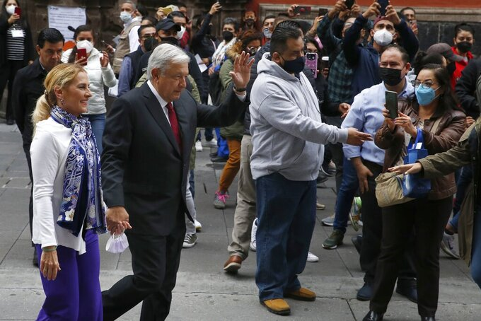 Mexico's President Andres Manuel Lopez Obrador waves to supporters as he walks with first lady Beatriz Gutierrez after voting in congressional, state and local elections in Mexico City, Sunday, June 6, 2021. Mexicans on Sunday were electing the entire lower house of Congress, almost half the country's governors and most mayors in a vote that will determine if  Obrador's Morena party gets the legislative majority. (AP Photo/Marco Ugarte)