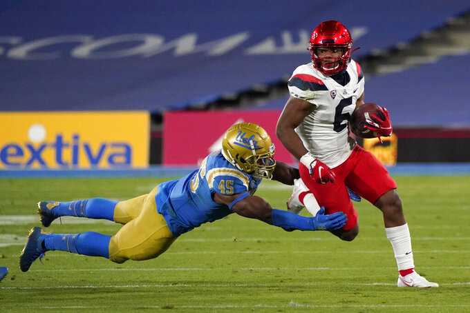 Arizona running back Michael Wiley (6) runs as UCLA linebacker Mitchell Agude (45) makes a tackle during the second half of an NCAA college football game Saturday, Nov. 28, 2020, in Pasadena, Calif. (AP Photo/Marcio Jose Sanchez)