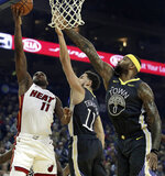 Miami Heat guard Dion Waiters, left, shoots against Golden State Warriors' Klay Thompson, center, and DeMarcus Cousins (0) during the first half of an NBA basketball game, Sunday, Feb. 10, 2019, in Oakland, Calif. (AP Photo/Ben Margot)