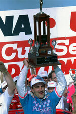FILE - Derrike Cope, from Spanaway, Washington, hoists his trophy in Victory Lane after winning the Daytona 500 auto race in Daytona Beach, Fla., in this Feb. 18, 1990, file photo. Cope is best known for winning the 1990 Daytona 500. At 62, Cope is back to give the Daytona 500 another try. (AP Photo/Kathy Willens, File)