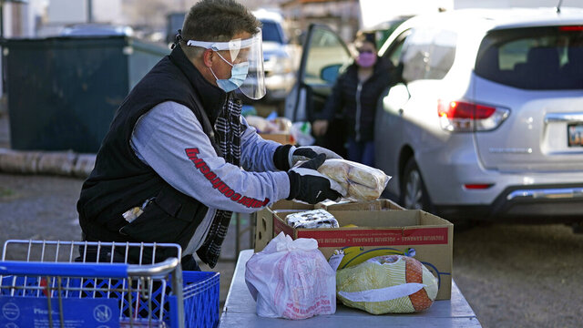 Food is loaded onto tables for those in need outside of the Catholic Community Services of Utah Friday, Nov. 20, 2020, in Ogden, Utah. As coronavirus concerns continue, the need for assistance has increased. (AP Photo/Rick Bowmer)