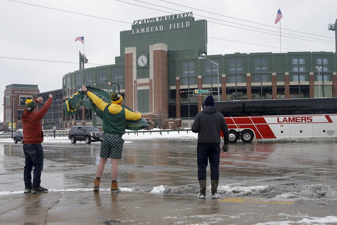 Packer fans react as team busses for the Tampa Bay Buccaneers arrive at Lambeau Field before the NFC championship NFL football game between the Tampa Bay Buccaneers and Green Bay Packers in Green Bay, Wis., Sunday, Jan. 24, 2021. (AP Photo/Mike Roemer)