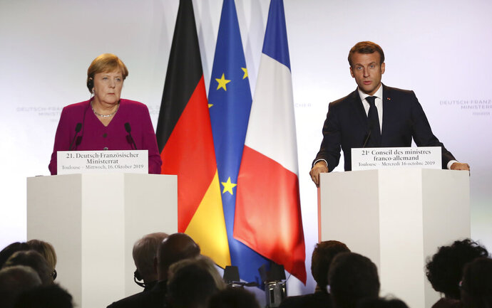 German Chancellor Angela Merkel, left, and French President Emmanuel Macron attend a media conference after joint Franco-German cabinet meeting in the government building of Toulouse, southwestern France, Wednesday, Oct.16, 2019. President Emmanuel Macron and Chancellor Angela Merkel sought Wednesday to demonstrate the solidity of the French-German relationship at a meeting in southern France, one day before a key EU summit that may approve a divorce deal with Britain.(AP Photo/Frederic Scheiber)