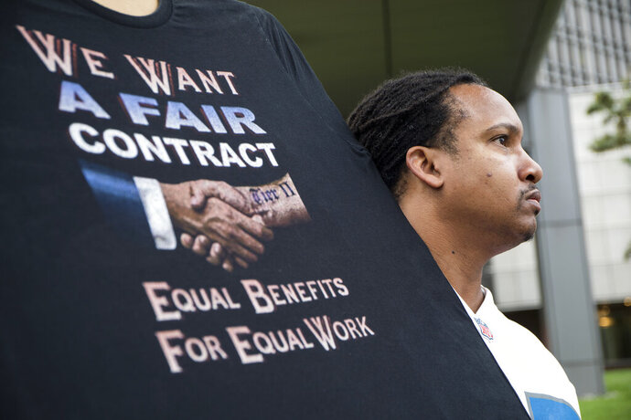 Sean Crawford, of United Auto Workers 598, rallies outside the Marriott Renaissance Hotel while the UAW GM Council holds a meeting inside the hotel in Detroit, Sunday Sept. 15, 2019. The new four-year deal between General Motors and 49,000 United Auto Workers will drive up the company's expenses with pay raises, bonuses and other increases. But analysts say GM is far better able to handle the expenses now than it was a decade ago, when the high cost of labor helped send it into bankruptcy protection. (Kathleen Galligan/Detroit Free Press via AP, File)
