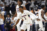 Connecticut's Alterique Gilbert (3) and Josh Carlton (25) celebrate at the end of an NCAA college basketball game against Florida, Sunday, Nov. 17, 2019, in Storrs, Conn. (AP Photo/Jessica Hill)