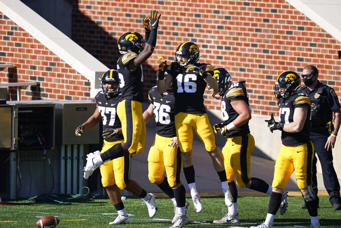 Iowa's Charlie Jones (16) celebrates with teammates after returning a punt 54-yards for a touchdown during the first half of an NCAA college football game against Michigan State, Saturday, Nov. 7, 2020, in Iowa City, Iowa. (AP Photo/Charlie Neibergall)