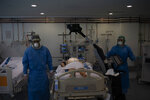 Healthcare workers prepare to x-ray a COVID-19 patient at a library that was turned into an intensive care unit (ICU) at German Trias i Pujol hospital in Badalona, Barcelona province, Spain, Wednesday, April 1, 2020. The new coronavirus causes mild or moderate symptoms for most people, but for some, especially older adults and people with existing health problems, it can cause more severe illness or death. (AP Photo/Felipe Dana)