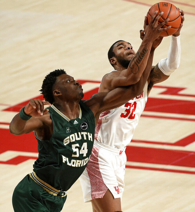 Houston forward Reggie Chaney (32) and South Florida center Russel Tchewa (54) vie for a rebound during the second half of an NCAA college basketball game, Sunday, Feb. 28, 2021, in Houston. (AP Photo/Eric Christian Smith)