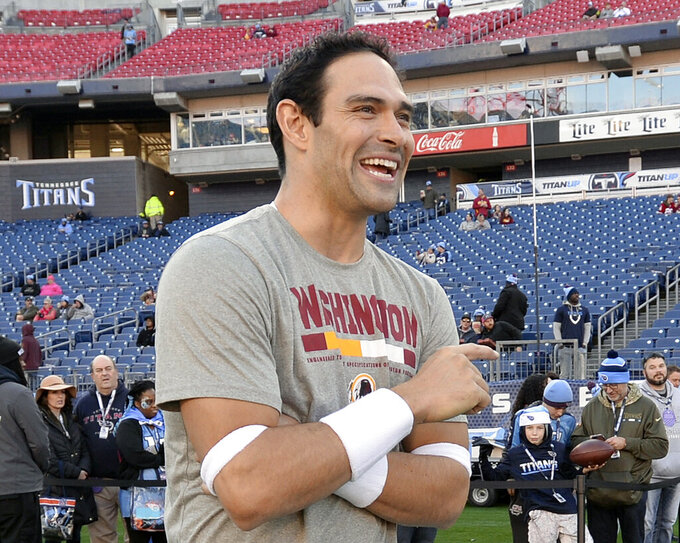 FILE - In this Dec. 22, 2018, file photo, Washington Redskins quarterback Mark Sanchez smiles before an NFL football game between the Redskins and the Tennessee Titans, in Nashville, Tenn. Former USC star and New York Jets first-round pick Mark Sanchez is retiring from the NFL and joining ESPN as a college football analyst. (AP Photo/Mark Zaleski, File)