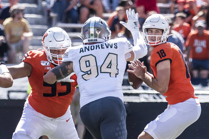 Illinois quarterback Brandon Peters (18) looks for a receiver as Eastern Michigan's Hunter Andrews (94) applies the pressure in the first half of a NCAA college football game between Illinois and Eastern Michigan, Saturday, Sept.14, 2019, in Champaign, Ill. (AP Photo/Holly Hart)