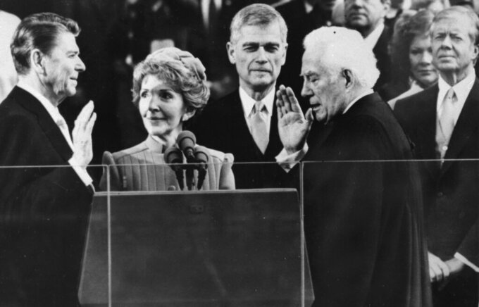FILE - In this Jan. 20, 1981, file photo Supreme Court Chief Justice Warren Burger administers the oath of office to Ronald Reagan, as Nancy Reagan holds the bible, at the Capitol in Washington. Outgoing President Jimmy Carter and wife Rosalynn look on at right. (AP Photo/Bob Daugherty, File)