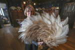 Anne Hoguet, 74, fan-maker and director of the hand fan-making museum poses with a feather fan at the museum in Paris, Wednesday, Jan. 20, 2021. Just like the leaves of its gilded fans, France's storied hand fan-making museum could fold up and vanish. The splendid Musee de l'Eventail in Paris, a classed historical monument, is the culture world's latest coronavirus victim. (AP Photo/Michel Euler)