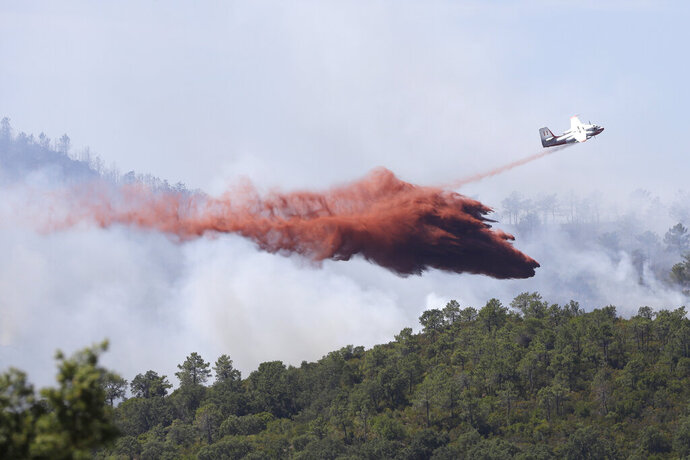 FILE - In this file photo dated Wednesday, July 26, 2017, a firefighting plane drops fire retardant over a forest near La Londe-les-Maures on the French Riviera, after authorities ordered the evacuation of 10,000 people as fires hopscotched around the Riviera for a third day.  Forest blazes are growing in intensity, especially in southern European countries and the European Union describes wildfires as