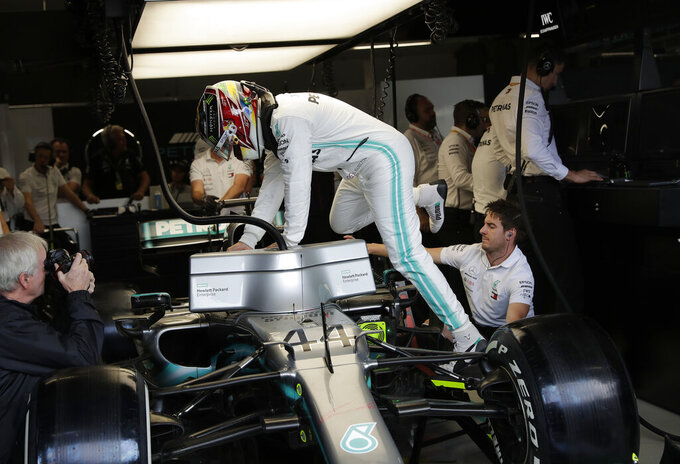 Mercedes' driver Lewis Hamilton, of Britain, climbs into his car during the first free practice at the Interlagos race track in Sao Paulo, Brazil, Friday, Nov. 15, 2019. Brazil Formula 1 GP will take place on Sunday.  (AP Photo/Silvia Izquierdo)
