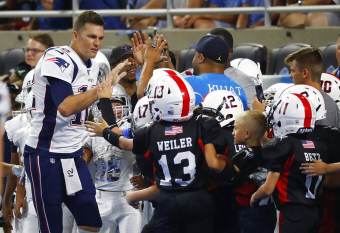 New England Patriots quarterback Tom Brady greets junior football players, who played during halftime of the Patriots preseason NFL football game against the Detroit Lions, Thursday, Aug. 8, 2019, in Detroit. (AP Photo/Paul Sancya)