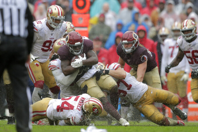 Washington Redskins running back Wendell Smallwood is tackled by San Francisco 49ers defenders as he rushes the ball in the second half of an NFL football game, Sunday, Oct. 20, 2019, in Landover, Md. (AP Photo/Julio Cortez)