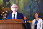 FILE - In this June 20, 2019, file photo, Wisconsin Gov. Tony Evers is surrounded by Democratic lawmakers and members of his Cabinet at a Capitol news conference in Madison, Wis. The Wisconsin Institute for Law and Liberty filed a lawsuit Wednesday, July 31, 2019, on behalf of three taxpayers, asking the Wisconsin Supreme Court to dramatically scale back the ability of governors to change the intent of lawmakers through partial budget vetoes. It is the most aggressive challenge yet to vetoes made by Evers to the state budget approved by the Republican-controlled Legislature in late June.  (AP Photo/Scott Bauer, File)