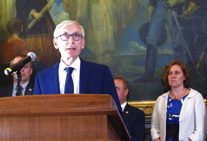 FILE - In this June 20, 2019, file photo, Wisconsin Gov. Tony Evers is surrounded by Democratic lawmakers and members of his Cabinet at a Capitol news conference in Madison, Wis. A conservative think tank has filed a federal lawsuit against Democratic  Gov. Evers, alleging that he violated First Amendment rights of staff members who were denied access to a press briefing. The MacIver Institute for Public Policy filed the lawsuit Tuesday, Aug. 7, 2019, in federal court in Madison  (AP Photo/Scott Bauer, File)