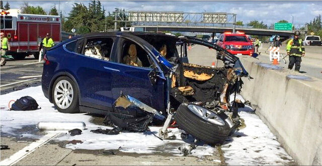 FILE - In this March 23, 2018, file photo provided by KTVU, emergency personnel work a the scene where a Tesla electric SUV crashed into a barrier on U.S. Highway 101 in Mountain View, Calif. The Apple engineer who died when his Tesla Model X crashed into the concrete barrier complained before his death that the SUV's Autopilot system would malfunction in the area where the crash happened. The complaints were detailed in a trove of documents released Tuesday, Feb. 11, 2020, by the U.S. National Transportation Safety Board, which is investigating the March, 2018 crash that killed engineer Walter Huang.  (KTVU-TV via AP, File)