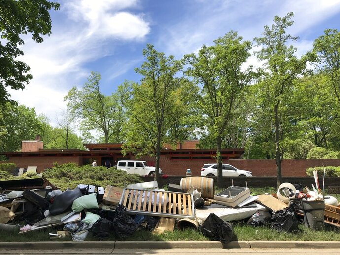 Piles of household debris line Valley Drive in Midland, Michigan, on Wednesday, May 27, 2020. The Central Michigan city, known for its midcentury modern architecture, was submerged after torrential rains overwhelmed two dams. Architecture enthusiasts worry how extensively the structures were damaged. (AP Photo/Tammy Webber)